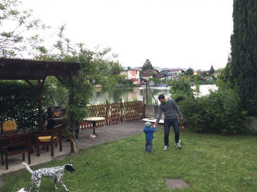Grillen und Ball spielen im Garten am See