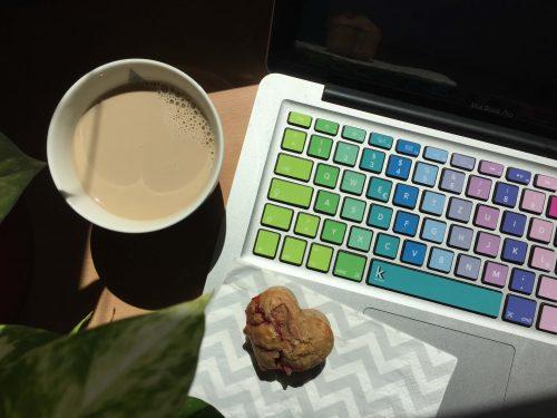 Kaffee und Muffin, neben bunter Macbook Tastatur