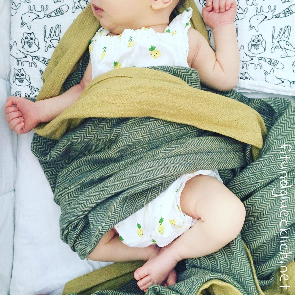 Baby liegt in Mamanuka Tragetuch eingewickelt